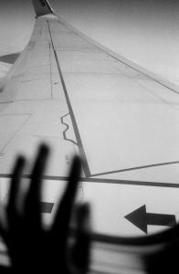 hand framför flygplansfönster