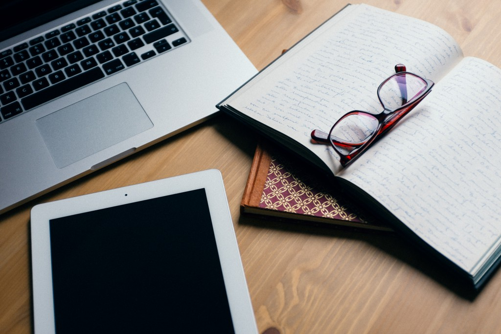 Dator, skrivblock, glasögon
