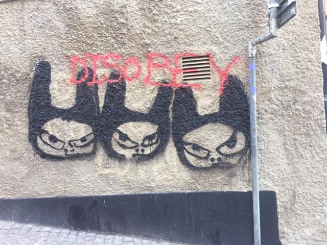 Graffiti med arga figurer och texten DIsobey.