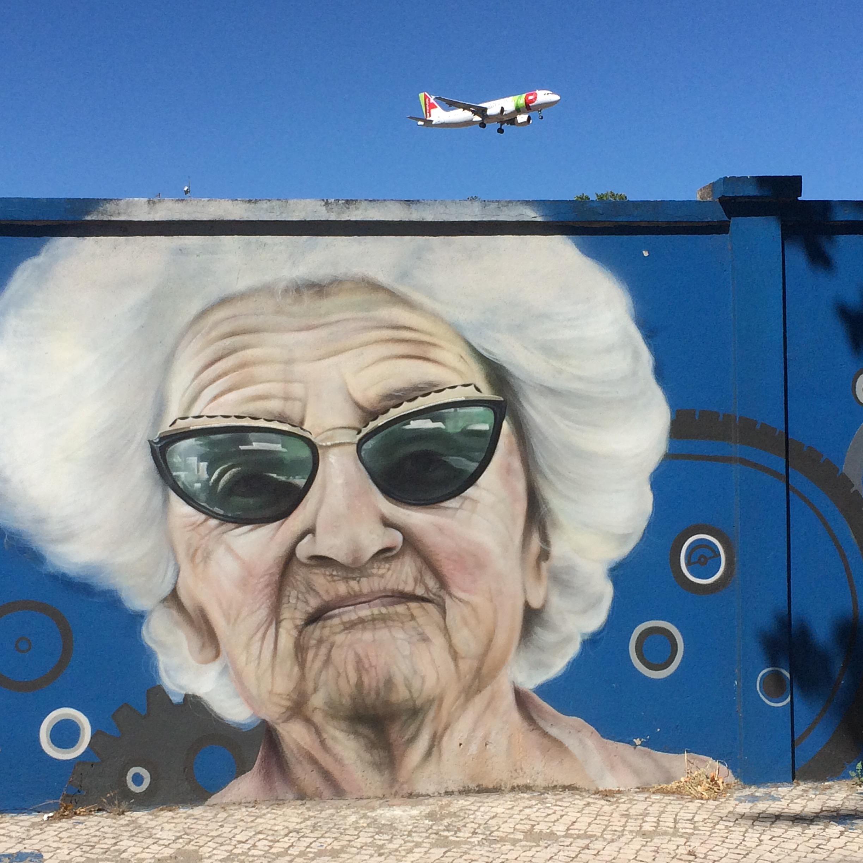 Graffitimålning på äldre dam, flygplan i bakgrunden. Lissabon